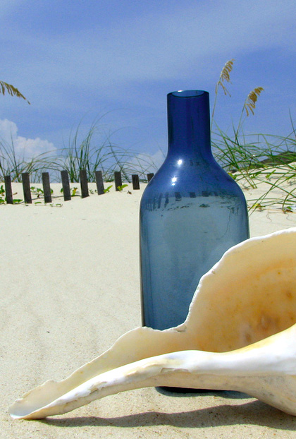 A shell and a green bottle over an empty beach